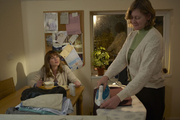 Rosemary Nicholls and her daughter Annette, played by Sarah Lancashire and Eva Birthistle respectively, chat as Rosemary does the ironing and Annette eats