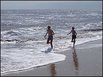 Two boys run along the sun-drenched beach