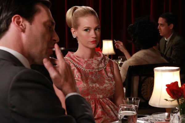 Don Draper, played by Jon Hamm, smokes in front of on-screen wife Betty Draper, played by January Jones