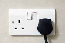 A three-pin plug in a wall socket