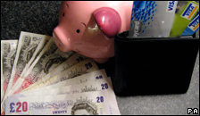 Bank notes, a piggy bank and a plastic card.