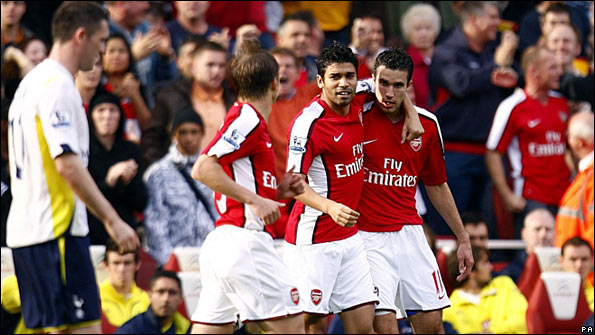 Arsenal celebrate their opening goal as Robbie Keane (left) looks on