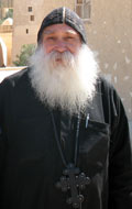 Father Ruwais, smiling Coptic monk in black robe and skull cap with large cross around his neck and a long white beard