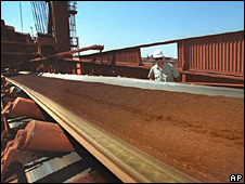 A conveyor belt filled with iron ore