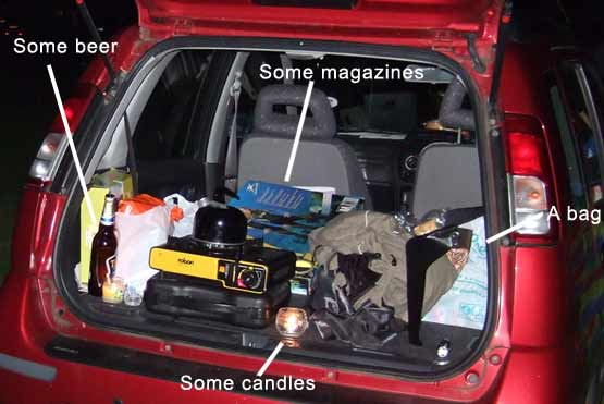 A car boot packed with things, including some beer, some magazines, some candles and a bag