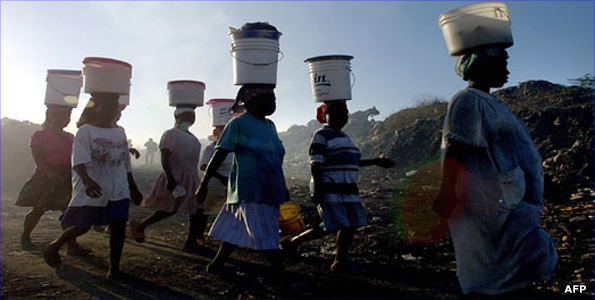 Women carrying buckets on their heads in Africa