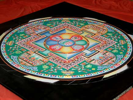 A view of the mandala, now close to completion. The pattern contains squares and circles and is symmetrical in four directions.  The dominant colour is green, with red, blue and yellow sand and many details in black and white.  The middle section represents a building and green areas nearer the edge resemble gardens filled with trees and other designs