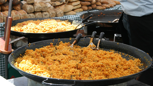 Large pans of rice being cooked at a market