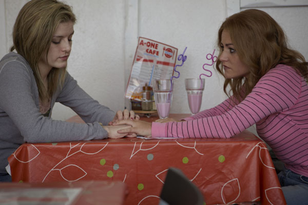 Gemma Adams and Anneli Alderton, played by Aisling Loftus and Jaime Winstone respectively, sit at a cafe table