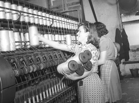 two female factory workers stand at spinning machine.