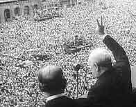 Photograph showing Winston Churchill waving to the gathered crowd on VE Day