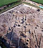Aerial view of the excavation site showing foundation marks in the mud