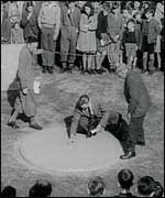 A black and white picture of men playing marbles