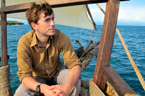 Simon Reeve in a boat on the Indian Ocean surrounded by blue water and blue sky