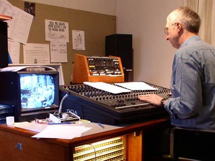 Looking over the shoulder of the sound engineer, who is balancing sound levels using the console in front of him.  A monitor on the desk shows the scene in the main room of the church.  On the far wall, a noticeboard displays a few clippings and cartoons, including one with the caption 'Tell me again how lucky I am to work here'