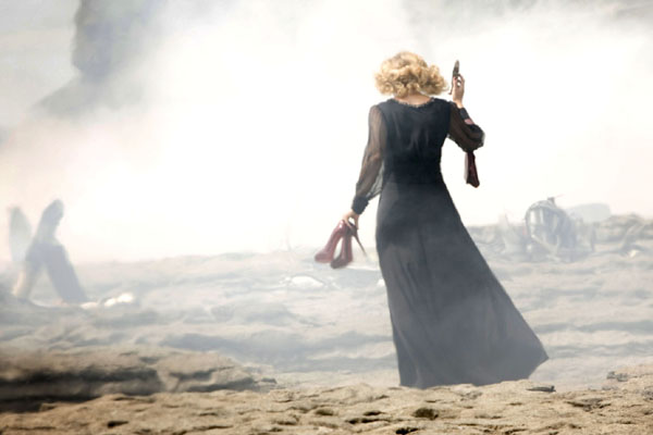 River Song, played by Alex Kingston, walks across the beach with red high heels in hand