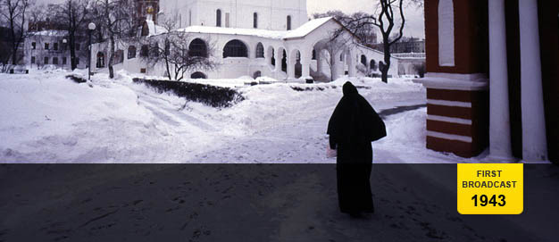 Woman in full length coat walking through snow towards convent in Moscow.