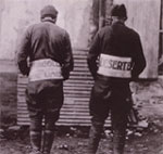 Photo of two American deserters wearing signs marking them as deserters