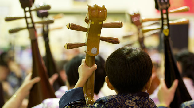 The back of a small child in traditional Chinese dress holding his instument as he plays along with the rest of the orchestra.
