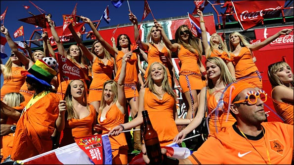 A group of women wearing orange mini-dresses