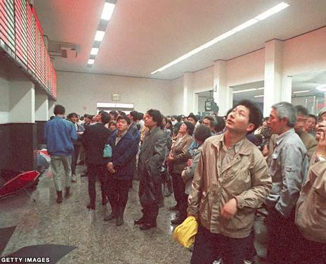 Picture of people looking up at the stock exchange board