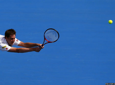 Germany's Florian Mayer misses a shot against Australia's Bernard Tomic during the Sydney International tennis tournament