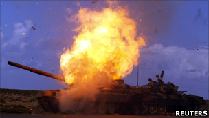 A tank belonging to forces loyal to Libyan leader Muammar Gaddafi explodes after an air strike by coalition forces