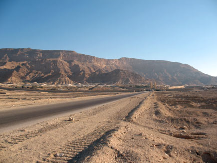 A road through the Egyptian desert.  Tyre marks can be seen in the sand on the tarmac.  In the distance a collection of low, light-coloured stone buildings is dwarfed by the red-brown mountains behind