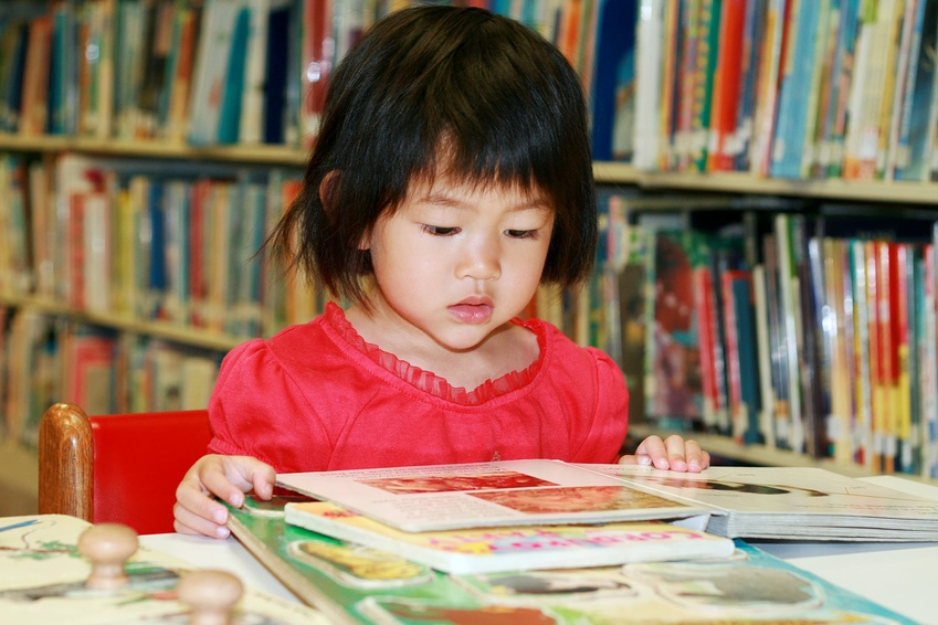 little girl reading book in library @ ying - fotolia