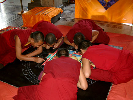 A wider shot shows five monks crowded around the mandala-in-progress, which is about two metres in diameter. They are kneeling on cushions placed around the tabletop, which is close to ground level