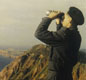 Keeping watch. A man stands on a cliff top, with binoculars to 'observe' or look out for enemy aircraft and ships.