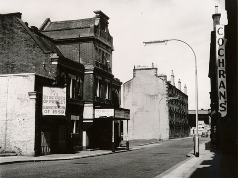 Black and white view along deserted street. A dilapidated theatre building to the left features a hoarding advertising the boy scouts of paisley gangshow of 1959. A raised railway line can be seen at the end of the street.