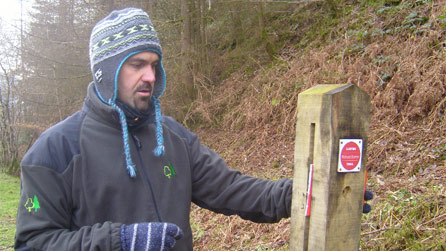 Jonathan Price, Ranger with the Forestry Commission with a vandalised sign.
