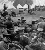 Black-and-white photo from 1915. Soldiers in First World War uniform sit on the ground, some looking at the camera, while a Church of England clergyman speaks. In the background are rows of tents