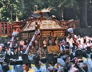 A gold-coloured mikoshi being carried by believers at a shrine
