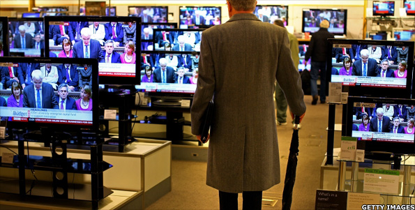 A man watching the chancellor deliver his speech on TV
