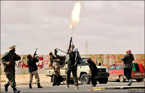 Libyan rebel fighters fire an anti-aircraft weapon at an airforce jet loyal to Colonel Gaddafi