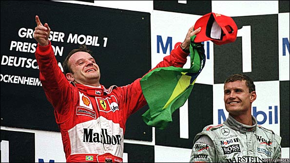 Rubens Barrichello celebrates winning the 2000 German Grand Prix, his maiden Formula 1 victory, watched by McLaren's David Coulthard