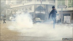 Protesters walk through tear gas during clashes with riot police in downtown of the capital Tunis January 14, 2011.