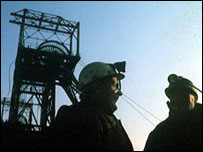 Pithead and miners silhouetted against a blue sky