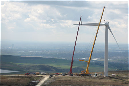 Crane attaching blade to wind turbine
