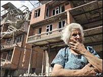 Lady outside damaged building in Gori, Sout Ossetia