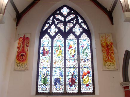 A tall stained glass window designed by William Morris, depicting eight saints.  On either side of the window are hangings showing a person with the flame of the Holy Spirit, captioned 'Prayer'