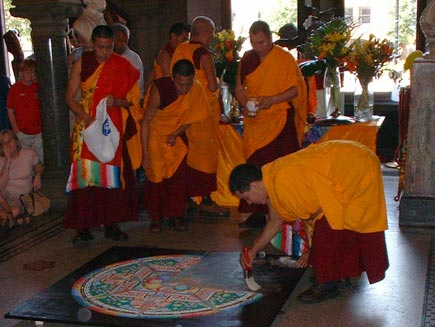 A quarter of the mandala has now gone. A monk is sweeping the sand up using a large paintbrush, working from the outside edge inwards
