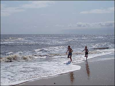 Boys running along the beach at Winterton