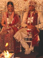 Hindu wedding ceremony in which bride and groom sit on chairs before the ceremonial fire