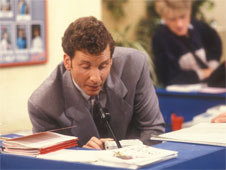 Still from sitcom 'The Brittas Empire'. Gordon Brittas speaks to his staff using an overhead speaker system.