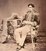 Emperor Meiji, a Japanese man in formal military dress, sits back in a fancy antique chair.  A fringed hat like that of a military commander can be seen on the table next to him and the upholstery, carpet and tablecloth are richly patterned