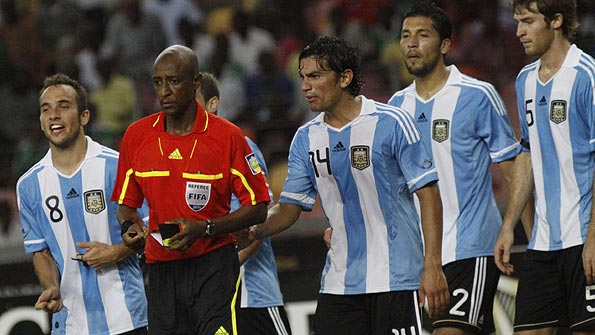 Referee Ibrahim Chaibou, in the red top, is surrounded by Argentina players after he awarded a penalty against them in the 4-1 defeat by Nigeria, in Abuja.