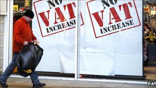 Man walking infront of a Sports Direct store in Liverpool advertising no VAT increase in their store